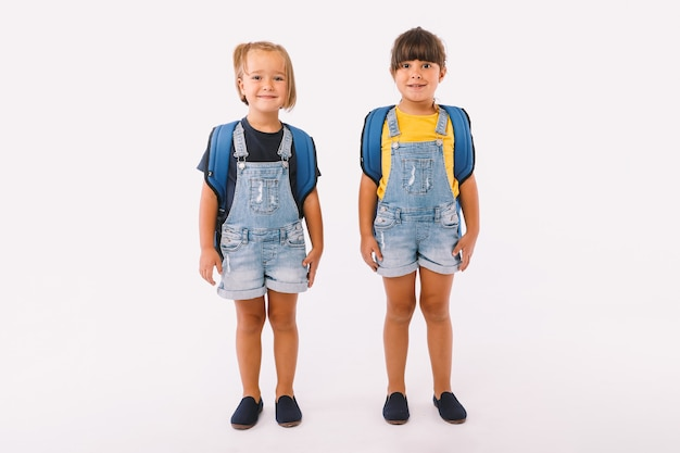 Twee kleine meisjes, één met blond haar en de andere met zwart haar, gekleed in denimblauwe overalls, met een rugzak, klaar voor terug naar school, op witte achtergrond.