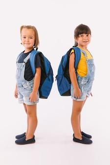 Twee kleine meisjes, een met blond haar en de andere met zwart haar, gekleed in denimblauwe overalls, met een rugzak, klaar voor terug naar school, zijwaarts, op een witte achtergrond.
