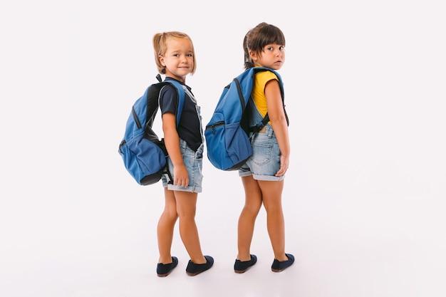 Twee kleine meisjes, een met blond haar en de andere met zwart haar, gekleed in een blauwe spijkerbroek, met een rugzak, klaar om terug naar school te gaan, met hun rug naar haar toe, op een witte achtergrond.