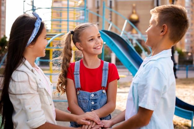 Twee kleine meisjes en een jongen die samen handen houden