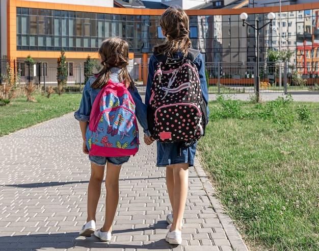 Twee kleine meisjes gaan naar school, hand in hand, achteraanzicht.