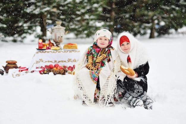 Twee kleine meisjes in bontjassen en sjaals in russische stijl op de zijne