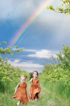 Twee kleine meisjes in bruine jurken rennen in de zomertuin op de achtergrondregenboog