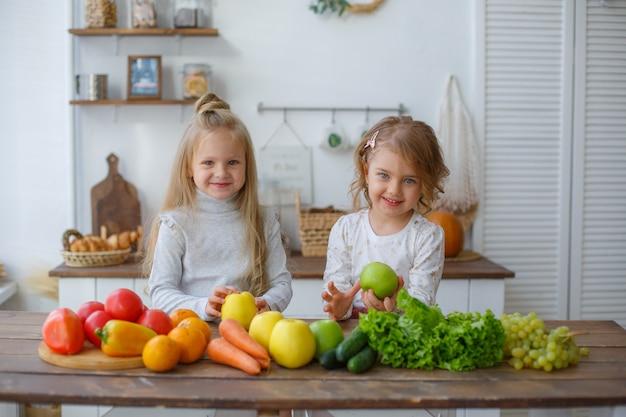Twee kleine meisjes in de keuken met groenten thuis