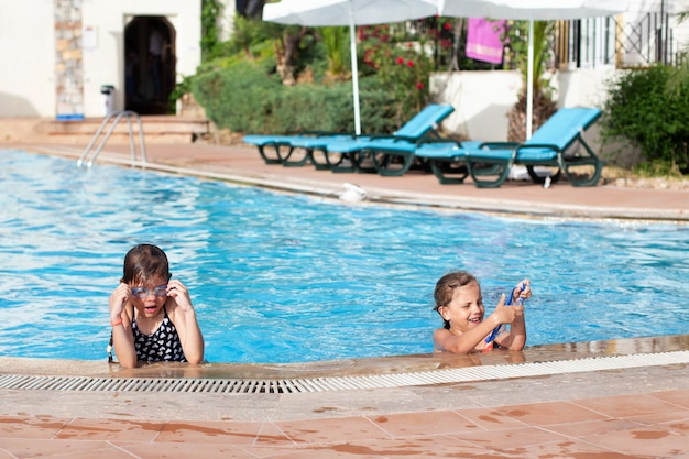 Twee kleine meisjes in glazen zwemmen in het zwembad