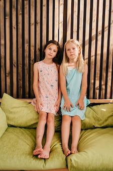 Twee kleine meisjes in mooie jurken zittend op citroen bed met houten muur achter hen
