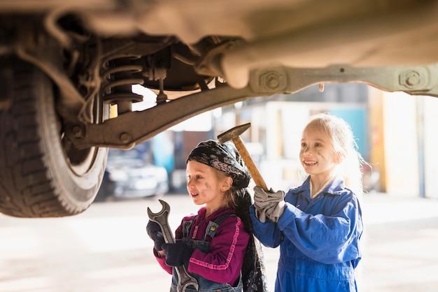 Twee kleine meisjes in overall staan met hulpmiddelen