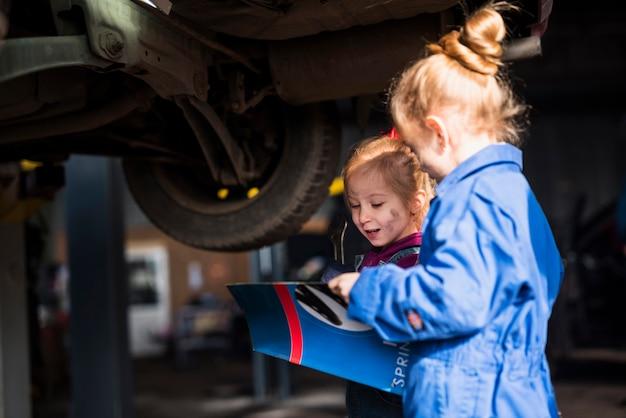Twee kleine meisjes in overalls met roermachinelegenmagazine