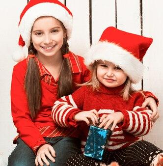 Twee kleine meisjes in rode hoeden zittend op de vloer met geschenken in de buurt van de nieuwe jaarboom