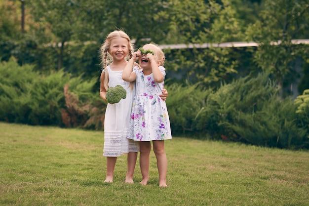 Twee kleine meisjes in sarafans en pigtails in een groene tuin houden broccoli in hun handen. ze sluiten hun ogen, lachen. gezond voedselconcept, groen vegetarisch voedsel.