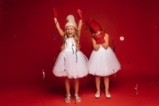 Twee kleine meisjes in witte jurken, mutsen en wanten strooien confetti op een rode achtergrond.