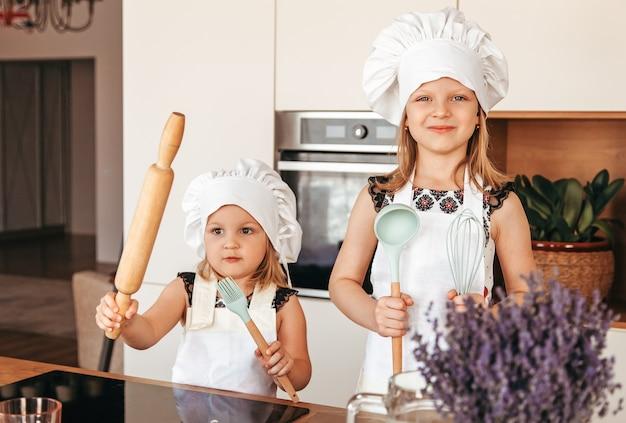 Twee kleine meisjes in witte schorten en koksmutsen in de keuken