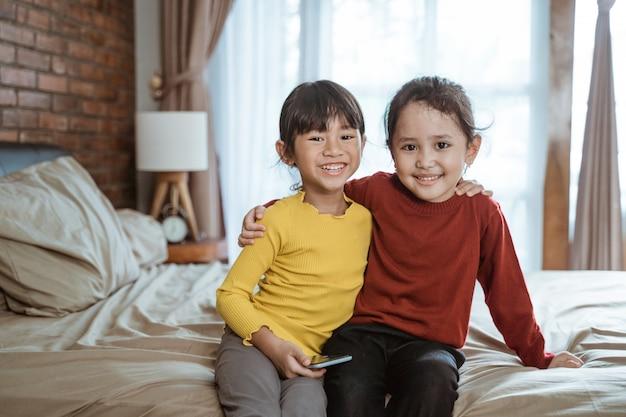 Twee kleine meisjes knuffelen elkaar lachen gelukkig kijken naar de camera