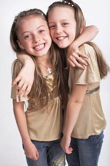 Twee kleine meisjes knuffelen elkaar
