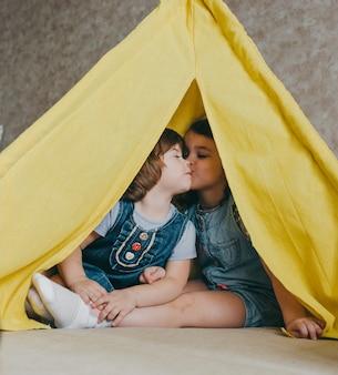 Twee kleine meisjes kussen elkaar in een gele tipi. kinderliefde van de zusters