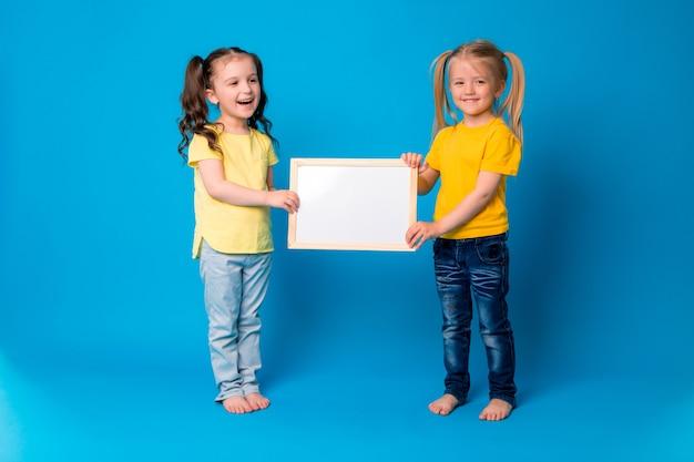 Twee kleine meisjes lachend met een lege tekentafel op een blauwe achtergrond