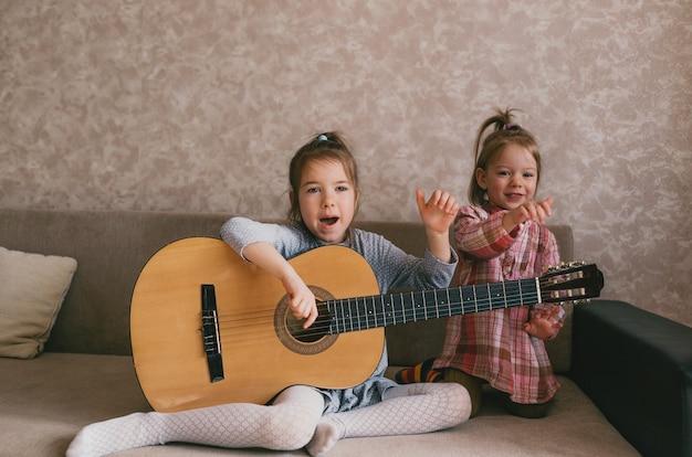 Twee kleine meisjes leren gitaar spelen, zingen liedjes terwijl ze thuis op de bank zitten