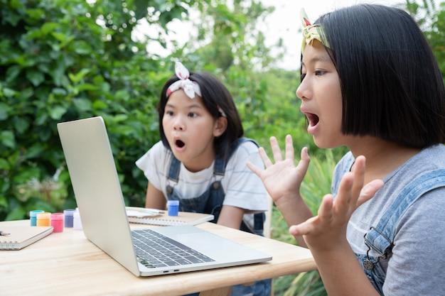 Twee kleine meisjes leren via online lessen in de voortuin. bescherm corona virus nieuwe stam of covid-19. onderwijs van thuis uit.