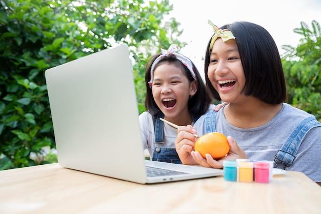 Twee kleine meisjes leren via online lessen in de voortuin.