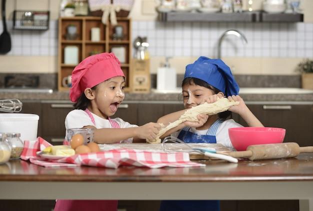Twee kleine meisjes maken pizza