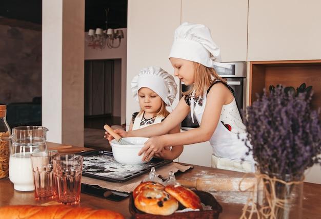 Twee kleine meisjes maken samen deeg in de keuken. zusters spelen in witte hoeden van de chef