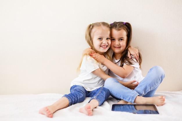 Twee kleine meisjes met behulp van een touchpad familie, kinderen, technologie en thuis concept