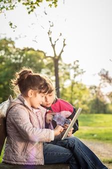 Twee kleine meisjes met behulp van tablet op de bank