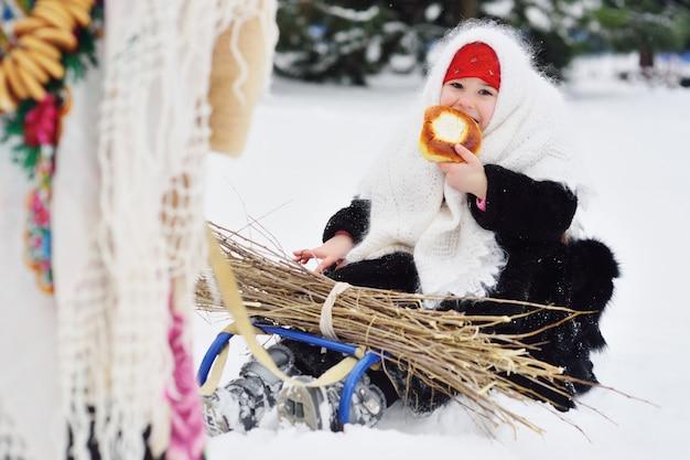 Twee kleine meisjes met bontjassen en sjaals in russische stijl worden gedragen op een slee armvol kreupelhout