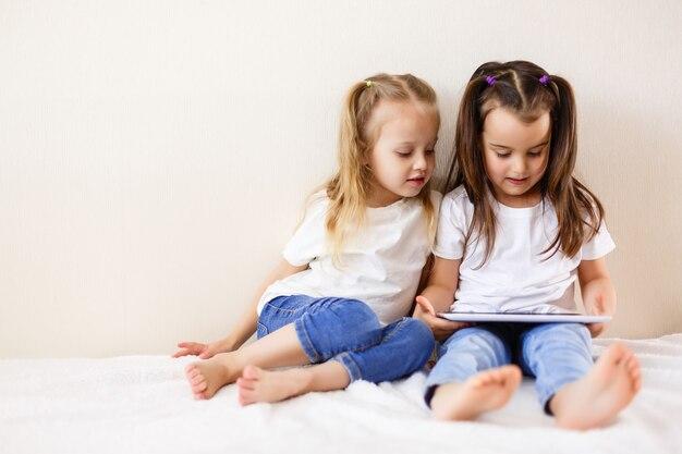 Twee kleine meisjes met een touchpad familie, kinderen,