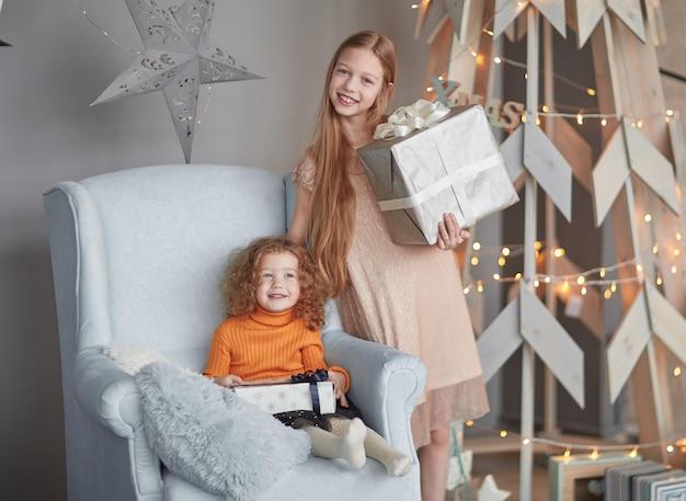 Twee kleine meisjes met geschenken staan in de buurt van een gestileerde kerstboom.