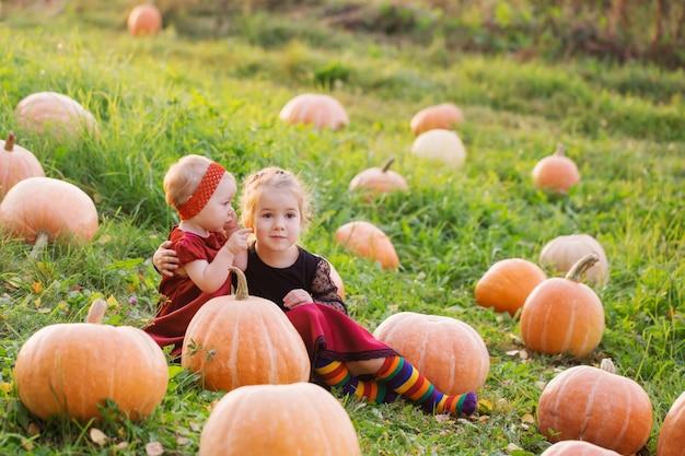 Twee kleine meisjes met oranje pompoenen bij zonsondergang