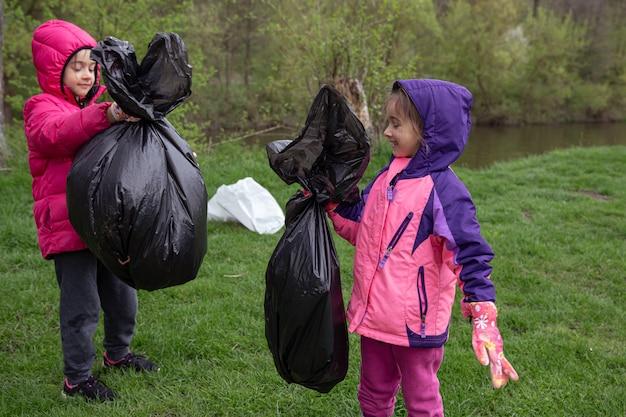 Twee kleine meisjes met vuilniszakken op reis naar de natuur, het milieu schoonmaken