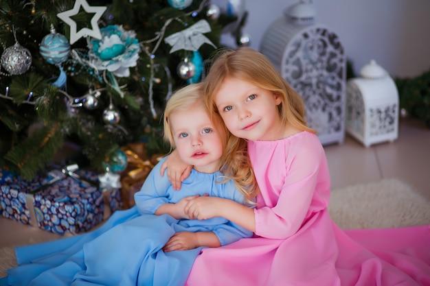 Twee kleine meisjes naast de kerstboom