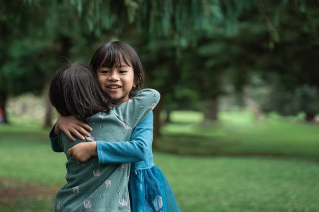 Twee kleine meisjes omhelzen elkaar vergeven