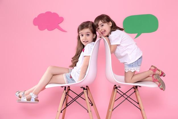 Twee kleine meisjes op gekleurd met spraak pictogrammen