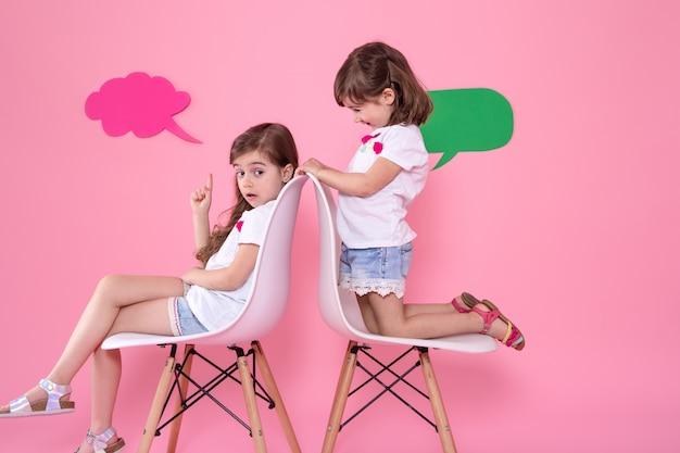 Twee kleine meisjes op gekleurde achtergrond met spraak pictogrammen
