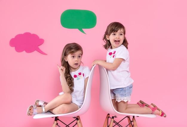 Twee kleine meisjes op gekleurde muur met spraak pictogrammen