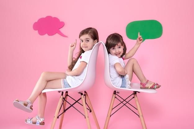 Twee kleine meisjes op gekleurde muur met spraakpictogrammen
