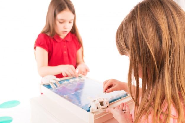 Twee kleine meisjes overwegen een kinderspel
