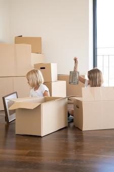 Twee kleine meisjes pakken dingen uit in een nieuw appartement, zitten op de vloer en nemen voorwerpen uit open cartoon dozen