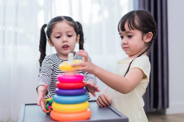 Twee kleine meisjes spelen kleine speelgoed ballen in huis samen. onderwijs en gelukslevensstijl