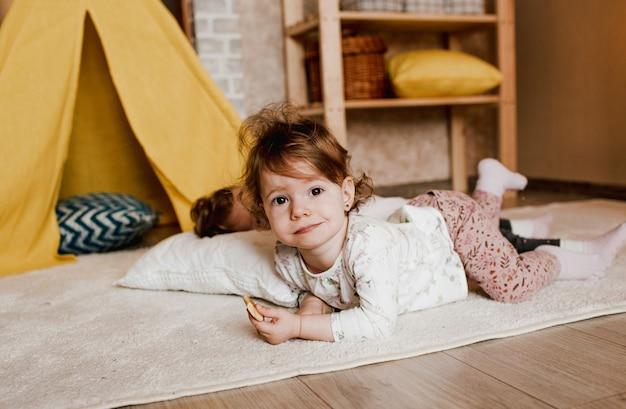 Twee kleine meisjes spelen liggend op de grond met koekjes in hun handen. gele wigwam