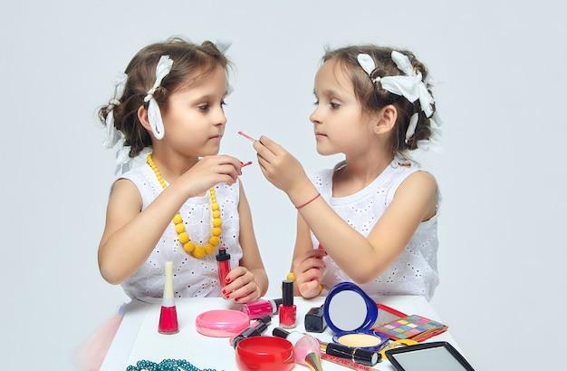 Twee kleine meisjes spelen met de make-up van hun moeder
