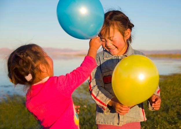 Twee kleine meisjes spelen met elkaar met ballonnen.