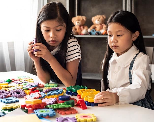 Twee kleine meisjes spelen samen plasticine, met geïnteresseerd gevoel, thuis studio, lens flare effect, wazig licht rond
