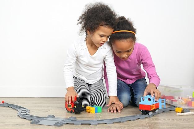 Twee kleine meisjes spelen speelgoedspoorweg