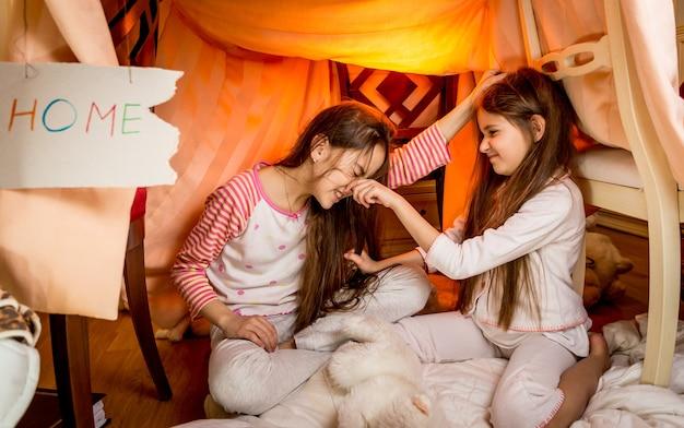 Twee kleine meisjes vechten op de vloer in de slaapkamer