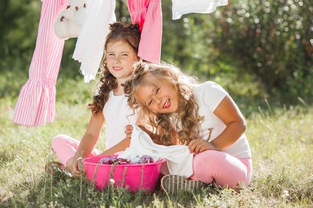 Twee kleine meisjes wassen. zusters die huishoudelijk werk doen