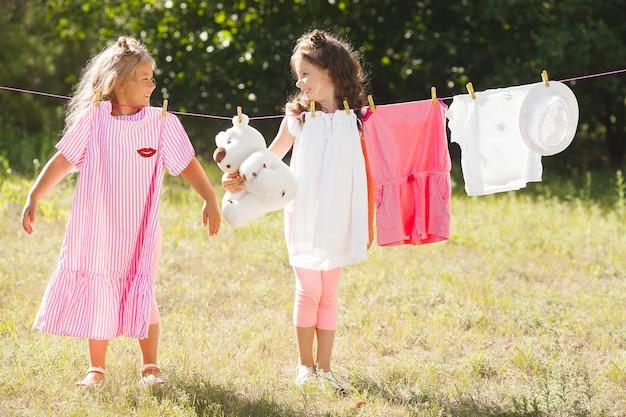Twee kleine meisjes wassen. zusters doen huishoudelijk werk