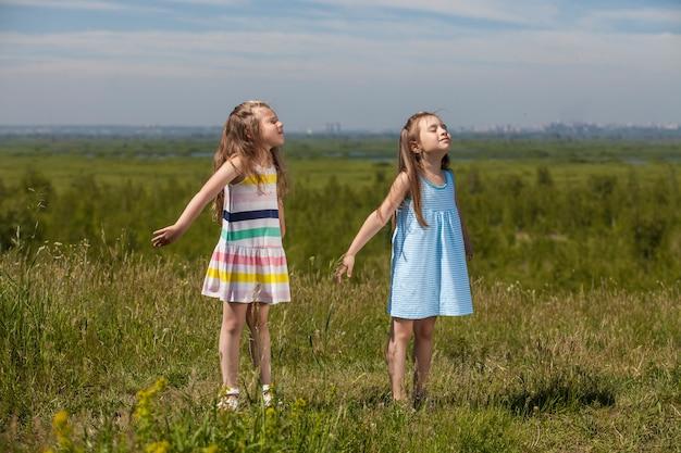 Twee kleine meisjes zijn mooie kinderen in de natuur die vrolijk in de zon glimlachen